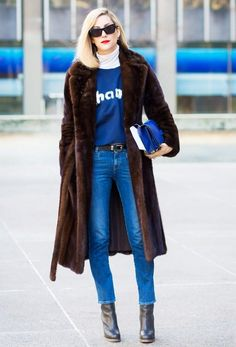 Joanna Hillman wears a turtleneck, graphic sweatershirt, brown fur coat, belted skinny jeans, black boots, black sunglasses, and a blue bag