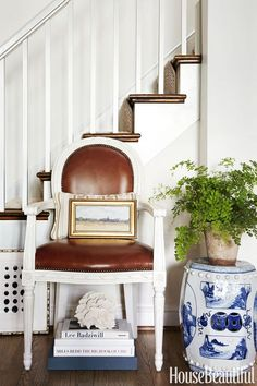 Sarah Bartholomew - House Beautiful A wonderful vignette under a staircase with a leather chair, landscape painting, and a blue and whi...