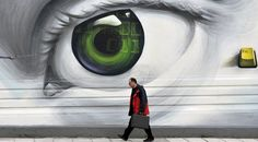 A man passes a decorated wall in Athens, Greece.