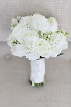 white hyacinth, cream roses, white ranunculus, and white tulips wrapped in ivory ribbon.