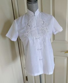 Vintage blouse, made in China ca. 1960s. Tag reads Size 34, by Daffodil. Unlined and semi-sheer.  White cotton/polyester blend Cheongsam blouse, hand embroidered with a floral motif. Metal snaps hide beneath traditional frog closures.  Measurements:  Length (shoulder to hem): 25  Bust: 18.5 flat (doubled to 37)  Waist: 18.25 flat (doubled to 36.5)  Hips: 19.5 flat (doubled to 39)  The tag reads size 34, but the measurements indicate that it would fit loosely on a modern size small or more…