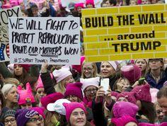 """No cartaz branco: """"Vamos lutar para proteger os direitos reprodutivos que nossas mães ganharam # Eu apoio a paternidade e maternidade programada"""". No amarelo: """"Vamos construir o muro... ao redor de Trump""""."""