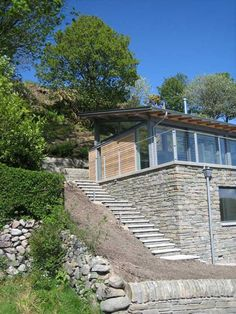 This stunning low energy house design by Simon Winstanley Architects has high eco appeal. Overlooking the Solway Firth in south-west Scotland, this slope house plan is built on a former...