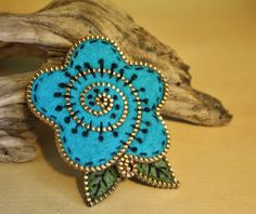 """Turquoise cabbage rose for your lapel. This brooch is made with recycled sweater felt and thrifted brass zipper pieces. The entire brooch has been hand embroidered... running stitches and french knots.The aprox. dimensions of this rose are 2 1/2"""" x 2 1/2""""."""