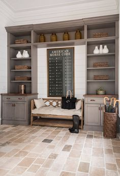 """This mudroom features limestone floor tiles and graywashed cabinets.  Limestone floor tiles are from Francois and Co.   Cabinet counters are made of reclaimed white oak. Notice the bench flanked by the gray cabinets.  Bench is Modena Bench by Gabby Home – $1,747.50  """"American Morse Code"""" poster is available through One Kings Lane. – $1,115.00"""