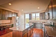 Townhome in Frederick, MD. This gourmet chef's kitchen features dark cabinets, light granite counter tops, hardwood flooring, recessed lighting, and stainless steel appliances including double ovens and a french door refrigerator. Click on the picture for the floor plans!
