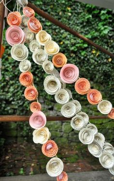 paper rose streamers via Lille Syster  Each flower was handmade and then artfully attached to braided hemp to create the garlands. The placement of each flower is carefully thought out so that it repeats in an effortless way. I really love these garlands!