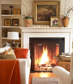 A roaring fire takes center stage in the living room of this New Hampshire home, furnished with a nubby cream sofa and white slipcovered chairs, both from Crate & Barrel.   - CountryLiving.com