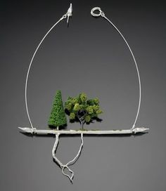 Artist and silversmith Sarah Hood combines miniature scale railroad materials like plastic trees, grasses, bushes and pebbles with sterling silver to culminate is one of a kind pieces that are nothing short of wearable art.
