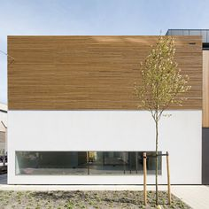 This 30 metre-long building alternates between one and two storeys-high and is clad in a chequered pattern of timber and white render.