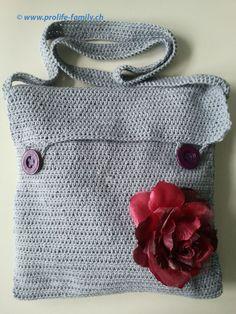 """graue Häkeltasche mit violetten Knöpfen und Futter und abnehmbarer Stoffblume - Zu finden auf www.prolife-family.ch in """"Shop für Afrika""""."""