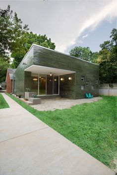 I like this for a variety of reasons: the variegated green glazed bricks; the built-in  bench and sink at the entry; the deep overhang creates a covered patio; the natural extension of the patio into the landscaping; the bold forms and colors.