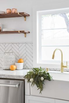 A Farmhouse Sink With Brushed Gold Gooseneck Faucet Is Positioned Beneath Window Partially Framed