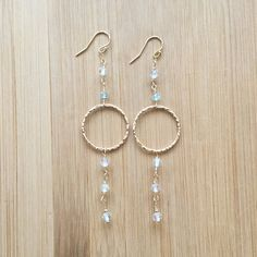 These shoulder length earrings in sparkling white topaz and 14K gold fill make for a stunning accessory. The white topaz and large gold filled circles are complemented by aquamarine gemstones, for a little something blue. The gemstones are wire wrapped by hand with 14K gold filled