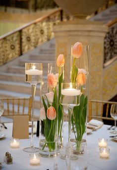 Vertical vases, tulips, and candles for centerpiece set