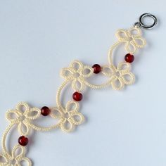 Very girly design in Valentine's Day colours. Cheerful flowery pattern brightened up by red beads. Unique handmade bracelet made using frivolite technique with a toggle clasp.