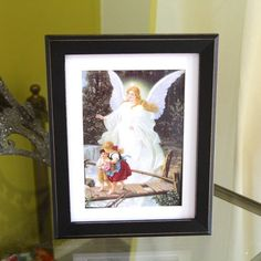 Guardian Angel Painting Framed Print.    This image is one that continues to be a Catholic favorite. Perfect for adding an angelic touch to a child's room or nursery, it now comes fitted in a calm black frame we love.