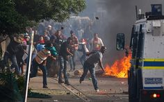 Residents of Masiphumelele throw rocks and petrol bombs at an armoured police    vehicle during a protest against the lack of policing in the Cape Town    township. According    to local reports  the protest was sparked by the court appearance of some    residents arrested in connection with vigilante killings.