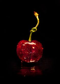 Deep red cherry, with the stem tied.) (My daughter can tie this in a knot with her tongue! Photo Fruit, Le Croissant, Fruit Photography, Simply Red, Shades Of Red, Food Art, Black Backgrounds, Color Splash, Red Color