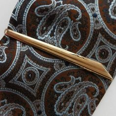 Vintage tie bar probably made around the 1950s Gold coloured metal with elegant minimalistic patterning This is the type of tie clip commonly called