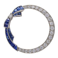 Antique Sapphire Diamond Platinum Circle Bow Pin. Feminine and graceful antique diamond circle pin. Set in platinum with applied square cut sapphire bow. Brilliant white diamonds weighing approx. 1.25 cts and 1ct of sapphires. Classic and chic. c 1905, US
