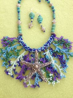 Coral stitched neck piece in shades of blue, lavender, green and turquoise.