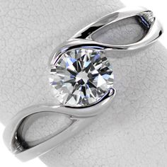 Motion - This sophisticated solitaire design features a 0.75 carat round brilliant cut diamond. The lustrous band creates a sense of flowing movement and embraces the center stone. The open pockets between the split shank keep the design delicate and maintain the fluid aesthetic.