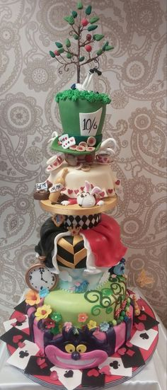 Alice in Wonderland Themed Event Cake Ideas- each layer touches on a classic Alice character - the Mad Hatter, Cheshire Cat, and the Queen of Hearts.