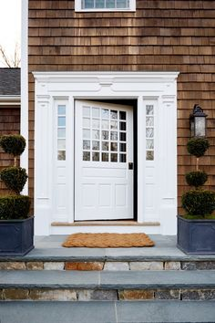 Bright white window trim and the paneled glass of the front door pop against the rich cinnamon hue of the home's shingled exterior.