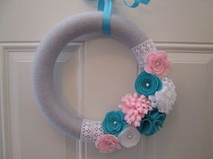 Sweet and pretty is the best words to describe this wreath! This wreath features light grey yarn with handmade felt flowers in 4 different styles