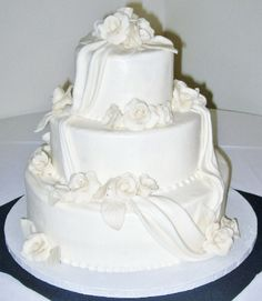 Buttercream iced wedding cake with modeling chocolate roses and fondant draping