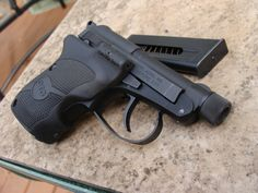 Customized Beretta 21A pistol. Note grips and threaded barrel