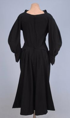 Black wool jersey with curved 3/4 sleeve having pinched and angled button cuff, bodice with curved seam incorporating sleeve in two pieces, straight center front seam split to form wired half collar, pencil skirt having two front pleats aligning with bodice seams, and angled folds over hip meeting at center of back over flaring back overskirt with bias cut silk faille lining having rows of diagonal stitching. Grosgrain interior waistband with hook and eye closure, partial silk lining.