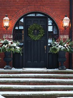 Traditional Front Door Christmas Decor - love the mixture of greenery in the urns.