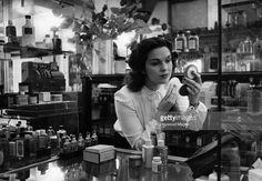 Joan, a sales assistant at Selfridge's department store, Oxford Street, London, makes up at the perfume counter. Original Publication: Picture Post - 4240 - A Girl Finds A Job To Suit Her - pub. 1946