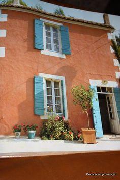 Paredes  rosé terracota e venezianas turquesa,cores acolhedoras;cortinas brancas rendadas e muitas flores......
