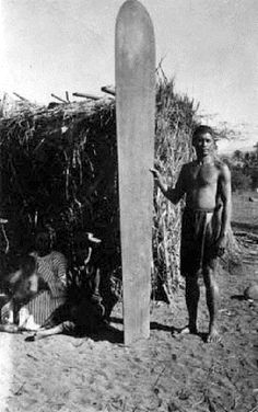 Native Hawaiian alaia surfer standing next a grass with his family in it. 1890