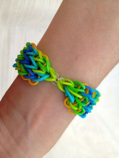 Rainbow Loom bracelet made from neon green, green, blue, light blue and dark yellow in the background - ArtyCraftySudio on Etsy