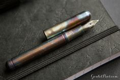 The Kaweco Liliput is a tiny fountain pen that when posted transforms into a full-sized pen that easily fits in your hand. This steel fountain pen features an amazing finish - each pen is hand-torched, which gives it a unique pattern of colors ranging from blue to purple to brown. Every pen is different! It comes with a stainless steel extra-fine nib and an ink cartridge to get you started writing right away! The cap screws on to the back to post securely. Accepts short standard…