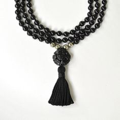 "Black Obsidian Mala Beads,  accented with Gold Pyrite Beads and a large Jet Guru Bead carved with Chinese Symbols.  Obsidian & Pyrite beads are 6mm Mala necklace measures 16"" in length (not including Guru Bead) and is 32"" in circumference. Carved Jet Guru Bead is approximately 20x10mm-Guru Bead and Tassel combined hang 2.5 inches long. Obsidian is quite protective, and is helpful in removing general negativity. It is also helpful for protection. It will also aid in eliminating bad habits."
