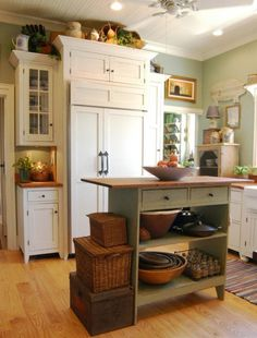 cottage kitchen love ~ Love the white cupboards, green island and lighter green walls.