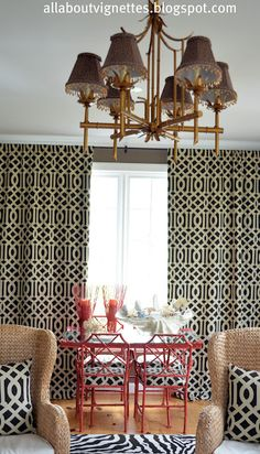 Hollywood Regency faux bamboo chandelier.  Room also has lattice window treatments, seat cushions on iron Chinese Chippendale chairs and pillows on seagrass wing chairs.  On the iron table with a mirrored top is a faux clam shell.  The table and chairs are painted Chinese Red.  A zebra rug is on the floor.  This room was featured on Nate Berkus http://www.youtube.com/watch?v=-G47OHEI4RM