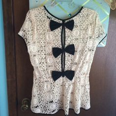 Crochet lace overlay Crochet laced shirt with black lining and black bows on the back. Flexible band built right under the last bow creating a flattering flair. Gently used Ryn Tops