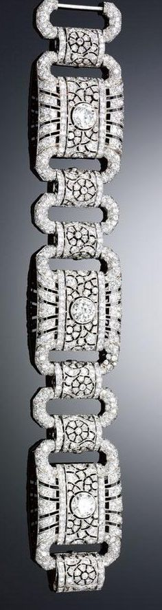 DIAMOND BRACELET, 1930S. Designed as a series of pierced rectangular plaques, each set with a principal circular-cut diamond within radiating surrounds of brilliant-cut diamonds, interspersed by open work links embellished with a flower head motif and similarly-set, length approximately 220mm.