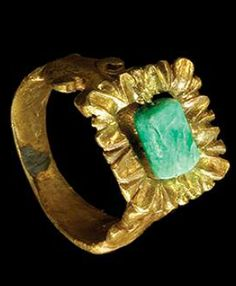 ROMAN GOLD FINGER RING SET WITH A CYLINDRICAL EMERALD BEAD on a gold pin within a crenelated, rectangular bezel, the shank with open scroll work at the shoulder to secure the bezel. Ca. 3rd Century AD.