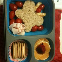 Super Easy Kid Bento Lunch: Container from Marshalls. Cut out sandwich with butterfly cookie cutter.  Make 5 slits in the middle of turkey slice, fold over lengthwise, roll end to end. Stack orange segments in a circle, then strawberry in the middle