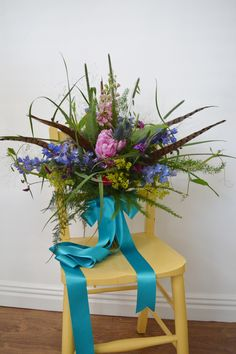 Wild, just picked, garden flower wedding bouquet. This large bridal bouquet was made using peonies, delphinium, larkspur, ferns and pheasant feathers tied with a long teal bow. www.wildandwondrousflowers.co.uk