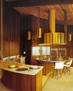 Mid-century modern.  The round kitchen, the slightly unusual set up was typical of this time. The brown colour scheme and timber also eludes to the era. https://emfurn.com/collections/eero-saarinen