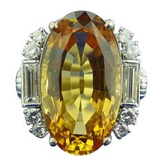 Art Deco Imperial Topaz Diamond Ring. An Imperial Topaz and Diamond Ring Mounted in Platinum. The ring features a 26.73 carat oval shaped topaz accented with baguette and round cut diamonds weighing approximately 1.55 carats in total. c 1935