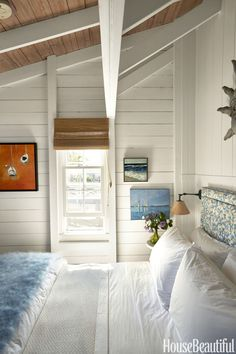 Paintings by local artists hang in the bedroom of this Nantucket boathouse, designed by Gary McBournie. The headboard is upholstered in Peter Fasano's Reef, and the Athena bed linens are by Yves Delorme. A handwoven mohair throw, by Nantucket Looms, lays on top of the bed.